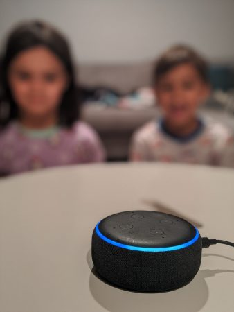 Two young children listen to a story told using Alexa.