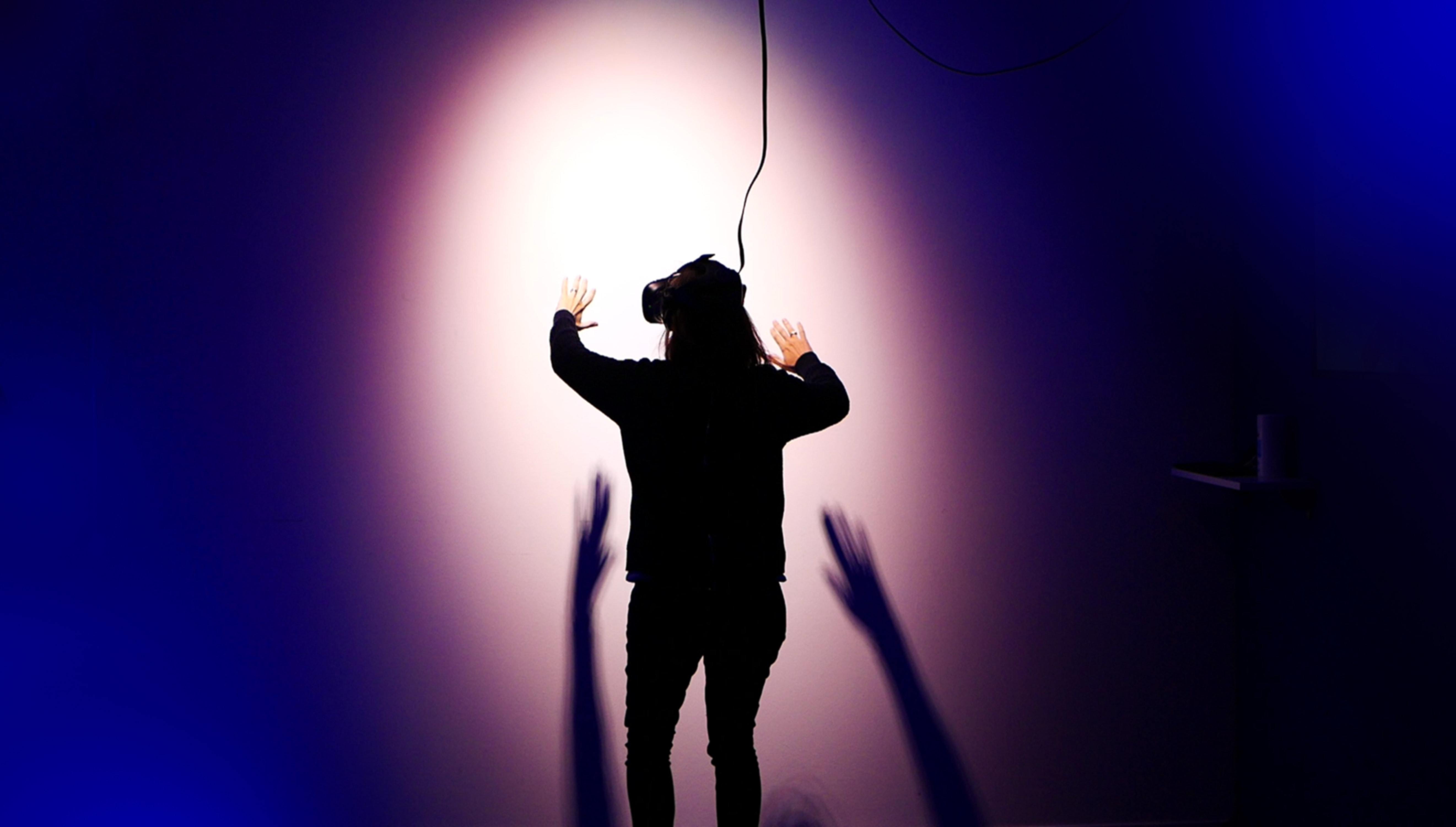 A photograph of a person experiencing a VR experience. They are wearing a VR headset, their hands are raised in front of them, casting a shadow. They are standing in front of a blurred purple and blue background as though on stage. They are facing away from the camera.